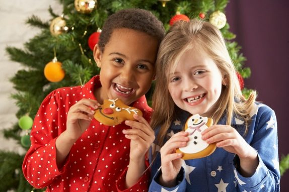 Two Young Children Eating Christmas Treats In Front Of Christmas